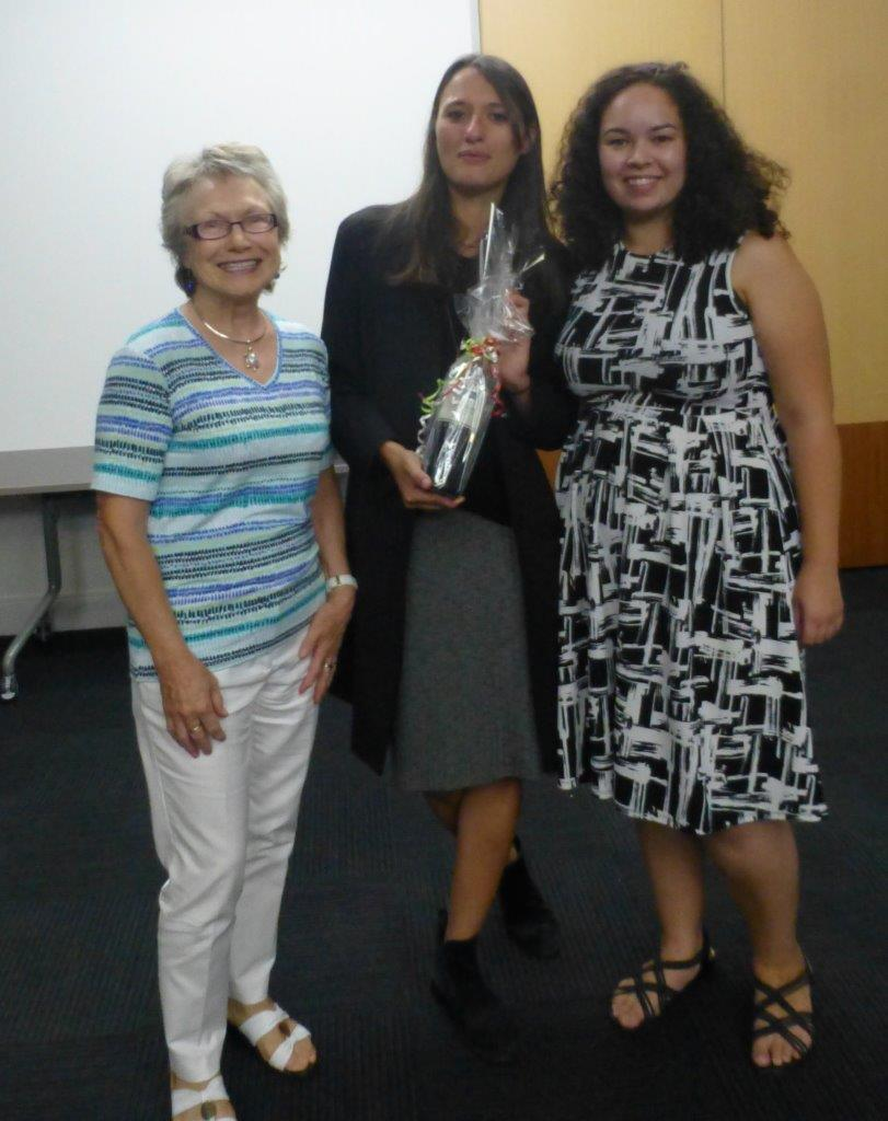 Sara D'Alessandro is presented with a bottle of wine by vice-presidents Yvette Devlin and Tamsin Hong