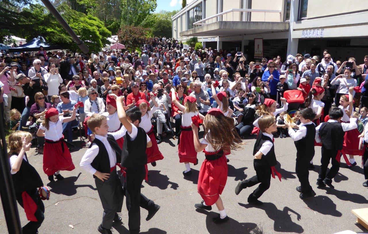 I bambini della scuola bilingue ballano la tarantella con tanta gioia, seguiti da una grande folla